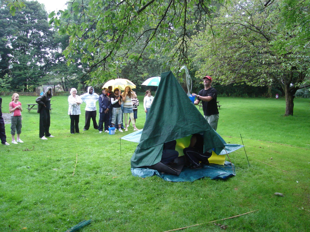 One of the facilitators tests the shelter built by young people in one of the design challenges