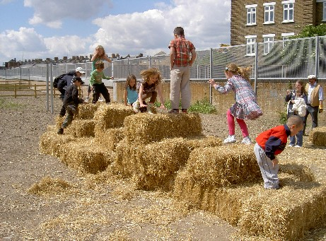 Children get stuck in building temporary spaces using the hay bales.